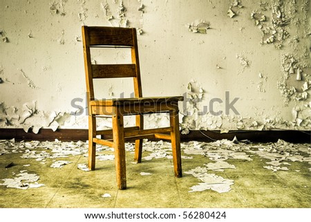Image of an old wooden chair in an abandoned building with cracked and peeling paint illuminated by natural daylight.