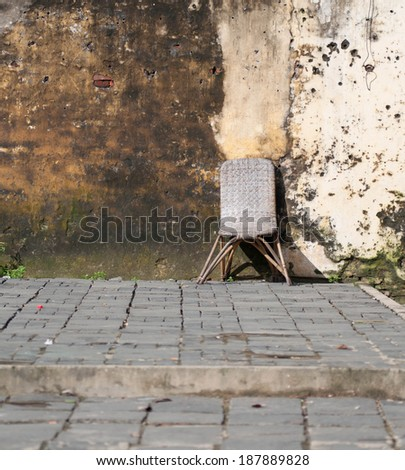Image of an old wooden chair outside of an abandoned building with cracked and peeling paint