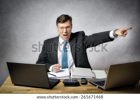 image of angry business man in suit who is screaming and pointing with finger in his office - stock photo