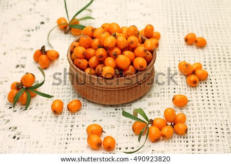 Image of appetizing sea buckthorn berries in wooden bowl
