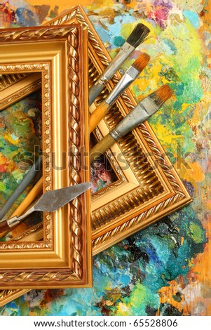 Image of artist's palette, paintbrushes and art frames - stock photo
