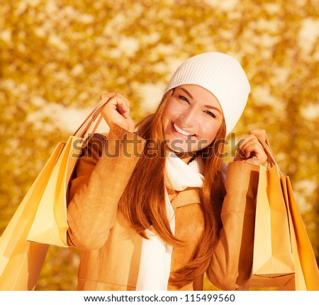Image of attractive cheerful woman with brown shopping bags on golden autumn background, closeup portrait of happy female enjoying gift bags, spending money concept, sales season - stock photo