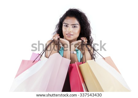 Image of attractive indian woman posing in the studio while holding shopping bags, isolated on white background - stock photo