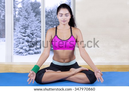 Image of attractive indian woman wearing sportswear and doing meditation on the mattress at home, shot with winter background on the window - stock photo