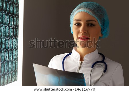 Image of attractive woman doctor holding x-ray results - stock photo