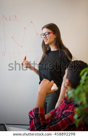 Image of beautiful businesswoman in glasses performing in board room in office interior. Real professional executive telling about new business projects, strategies and plans. - stock photo