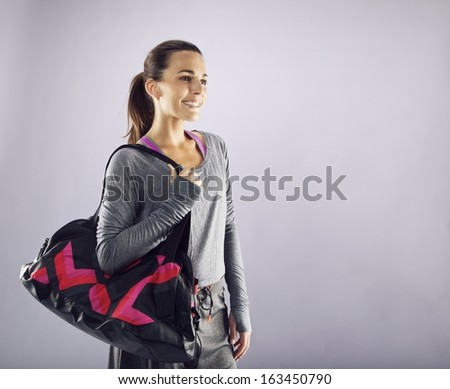 Image of beautiful caucasian female athlete with gym bag looking away smiling. Young woman in sportswear carrying gym bag looking at copyspace. - stock photo
