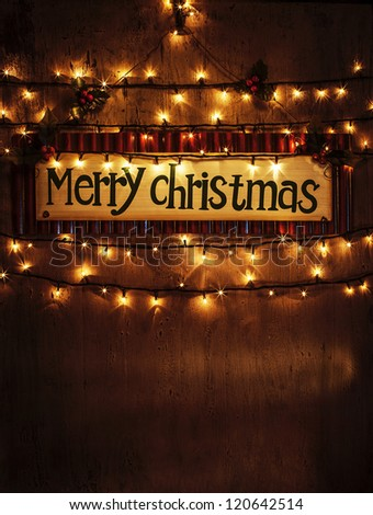 Image of beautiful Christmastime home decoration, Merry Christmas banner hanging on the door decorated with festive lights, x-mas ornament on dark brown grunge background, New Year greeting card - stock photo