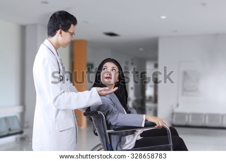 Image of beautiful disabled woman sitting on the wheelchair while talking with a doctor in the hospital corridor