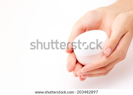 Image of beautiful female manicured hands holding cream