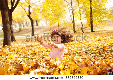 Image of beautiful girl jumping in the pile of autumn leaves, shallow depth of field