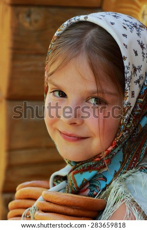 image of beautiful little girl in russian village traditional kerchief with round cracknel with russian ornamen over summer weather - stock photo