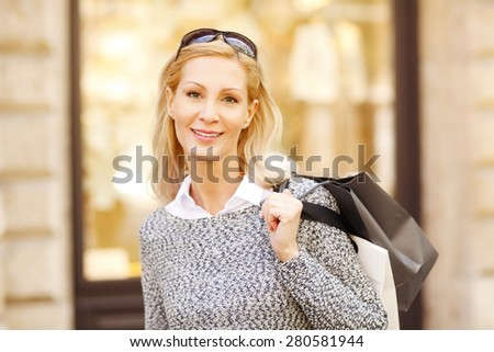 Image of beautiful smiling woman looking at camera and standing with her shopping bags in front of a store. - stock photo