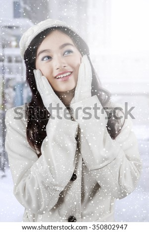 Image of beautiful teenage girl with beauty pose and wearing winter coat in snowy day at the city
