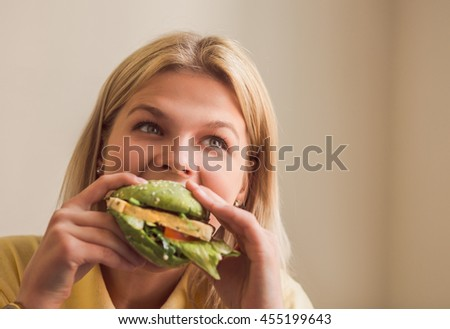 Image of beautiful woman eating vegan burger in vegan restaurant or cafe. Closeup picture of hungry lady eating healthy food. Vegan concept.
