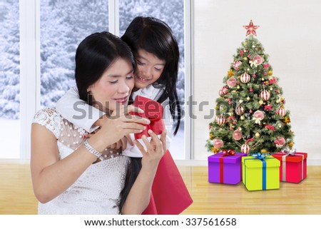 Image of beautiful young mother and her daughter opening christmas gifts at home - stock photo
