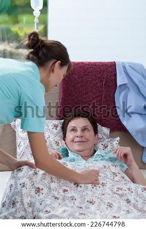 Image of bedridden woman and helpful nurse - stock photo