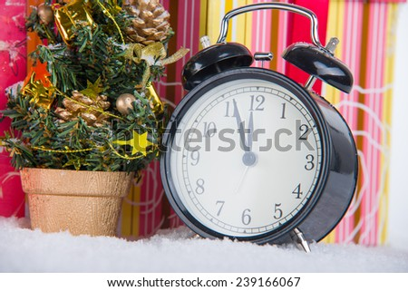 Image of Bell clock on snow with presents