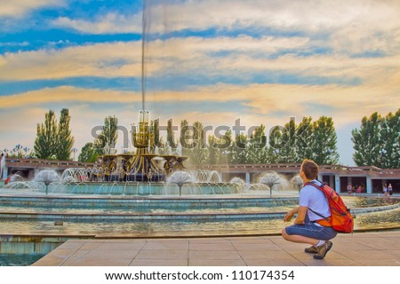 Image of big fountain in National Park of first President of Kazakhstan. Young tourist admiring the sunset scenery. Almaty - stock photo