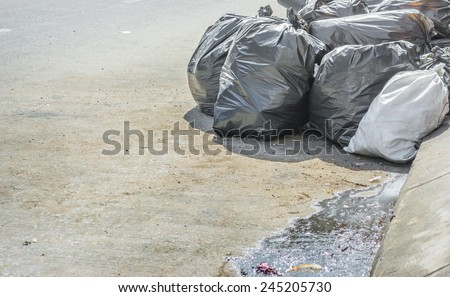 image of black garbage bag on the street. - stock photo