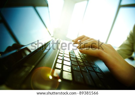 Image of black laptop keyboard with female hands over it - stock photo