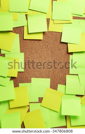 Image of blank green and yellow sticky notes on cork bulletin board - stock photo