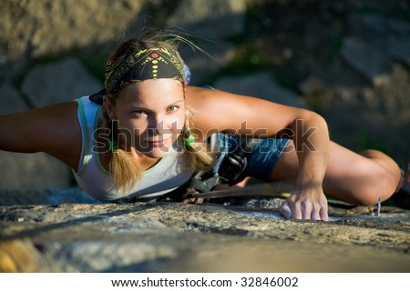 Image of blonde lady climbing on the rock - stock photo