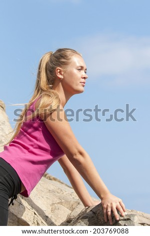 Image of blonde lady climbing on the rock. Fitness training - stock photo