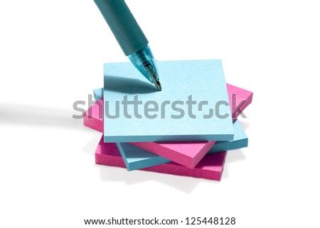 Image of blue and pink post it note paper with pen against the white background - stock photo