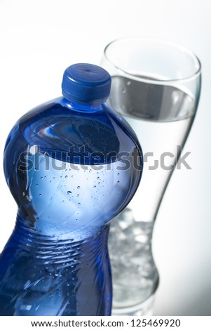 Image of blue water bottle and glass with ice and water in background.