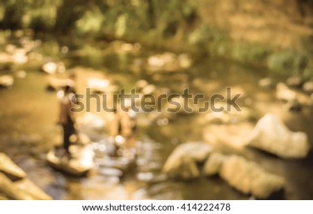 image of blur people at river and forest on day time for background usage . (vintage tone) - stock photo