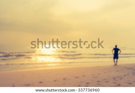 image of blur people walking on the beach with sunset for background usage . (vintage tone)