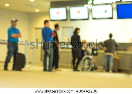Image of blurred people queuing up at the information service counter at the airport - stock photo