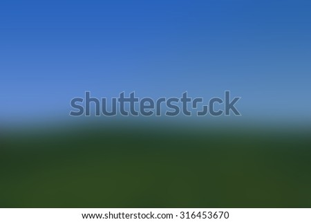 Image of blurry green grass field and bright blue sky - stock photo