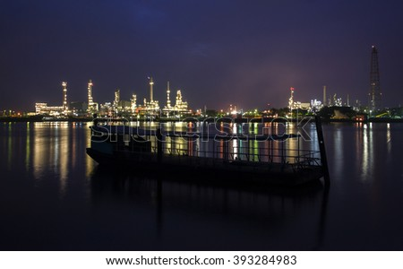 Image of blurry with soft bokeh lights Refinery plant with foreground boat and real water reflection in Bangkok