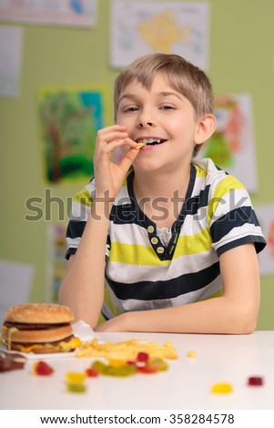 Image of boy having unhealthy caloric diet - stock photo