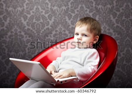 Image of boy sitting in a chair with a laptop - stock photo