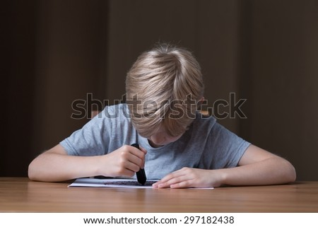 Image of boy with mental problems drawing with black crayon - stock photo