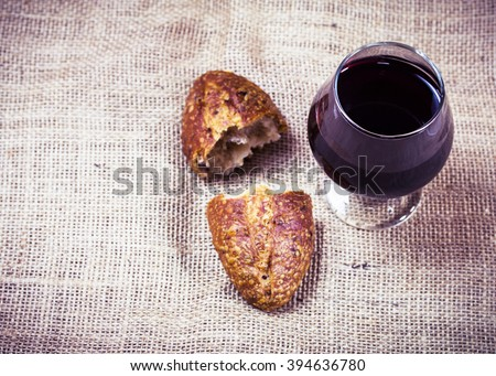 image of bread and a cup of grape juice  on sack cloth background with copy space, communion concept, Easter background - stock photo