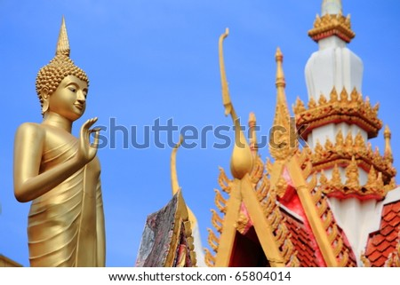 Image of Buddha with background of a temple gable - stock photo