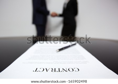 Image of business contract on background of business partners handshaking - stock photo