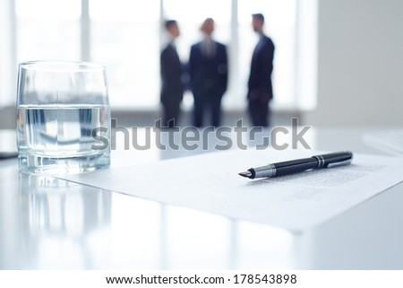 Image of business document, pen and glass of water at workplace with group of colleagues on background  - stock photo