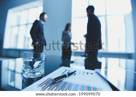 Image of business document, pen, glass of water and touchpad at workplace with group of business people talking on background - stock photo