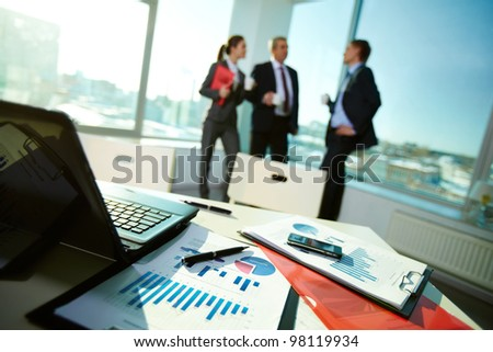 Image of business documents on workplace with associates talking on background - stock photo