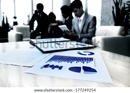 Image of business documents on workplace with partners interacting on background