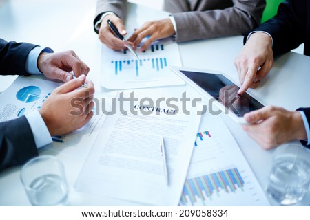 Image of business documents, touchpad, pen and glasses on workplace at meeting - stock photo