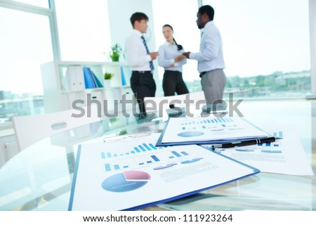 Image of business documents with working team communicating at background