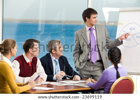 Image of business group listening attentively to their young colleague making presentation on board - stock photo