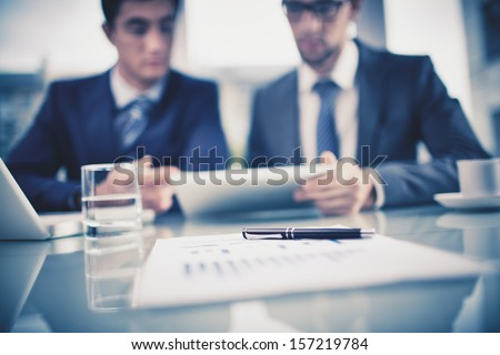 Image of business objects on background of two young businessmen discussing document in touchpad at meeting - stock photo