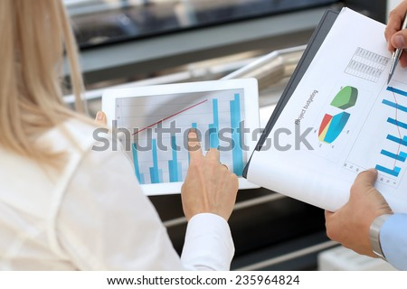 Image of business partners discussing documents and graphs  in the office - stock photo